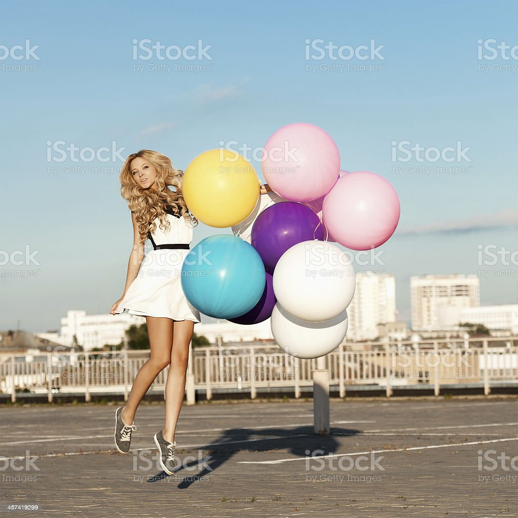 Happy young woman with colorful latex balloons royalty-free stock photo