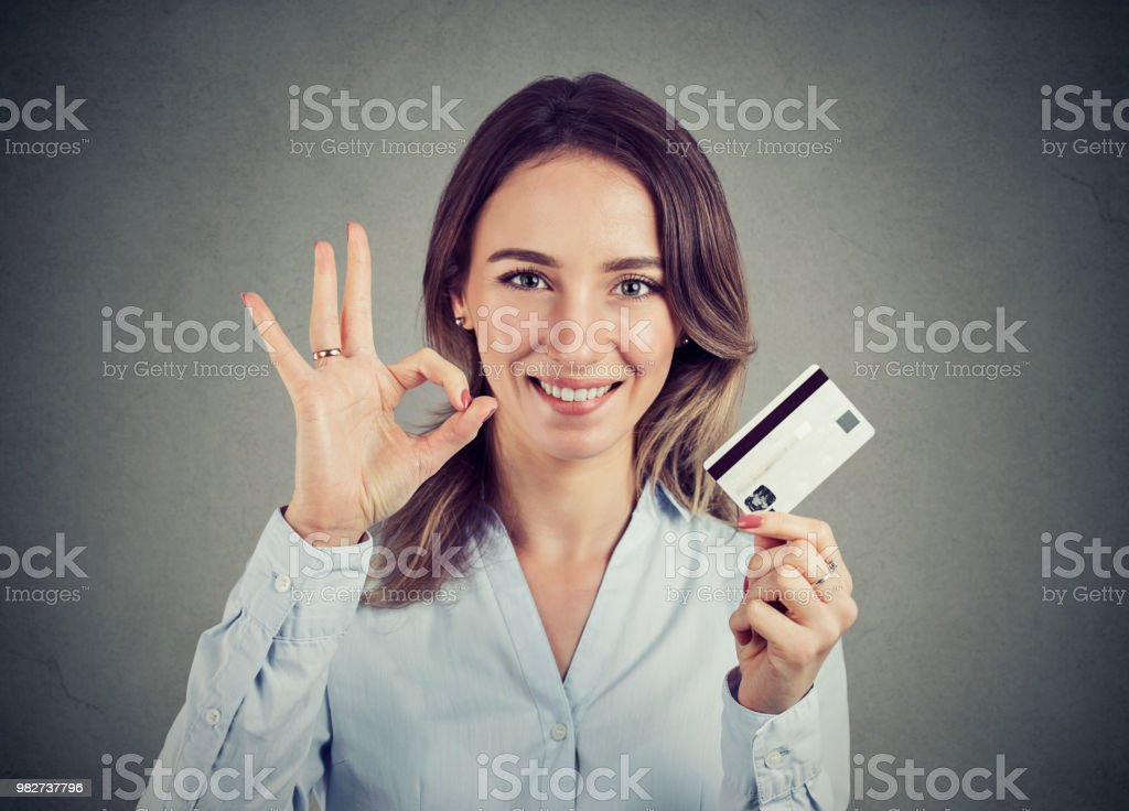 happy young woman with credit card giving ok hand sign gesture stock photo
