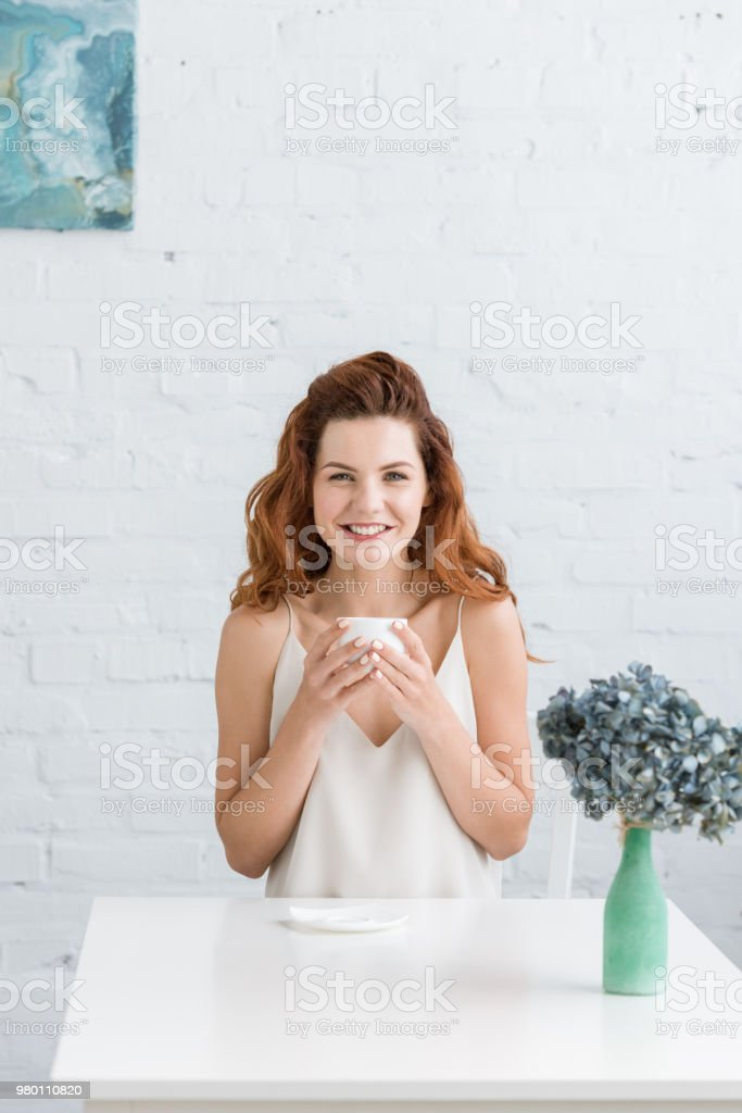 happy young woman with cup of coffee in front of white brick wall looking at camera stock photo