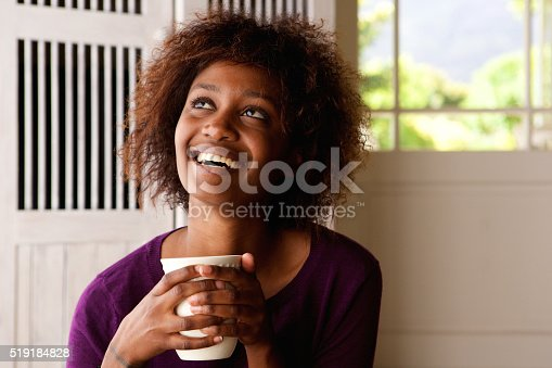 Close up portrait of a happy young woman with cup of coffee