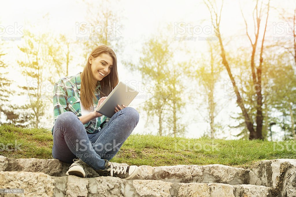 Happy young woman with digital tablet sitting in park stock photo