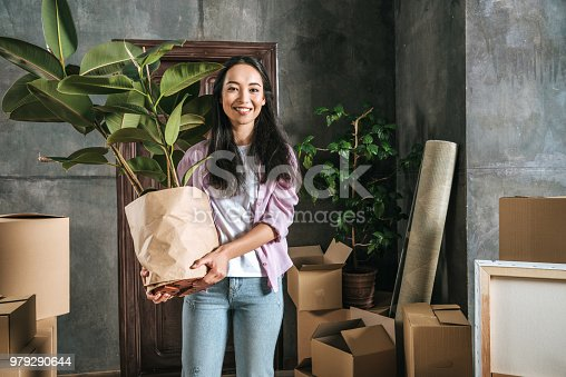 istock happy young woman with ficus plant and boxes moving into new house 979290644