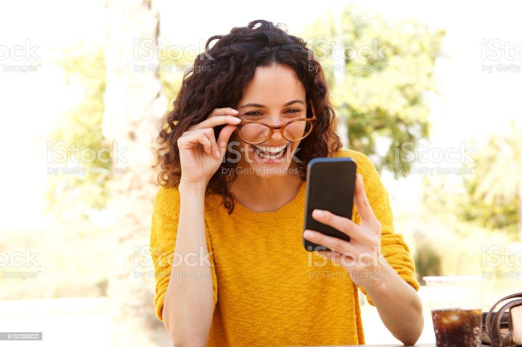 heureuse jeune femme avec des lunettes en regardant téléphone portable - Photo