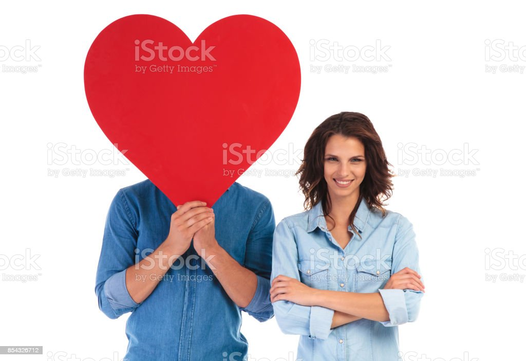 happy young woman with hands crossed standing near lover stock photo