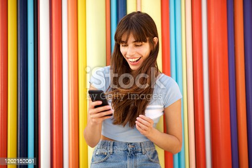 Portrait of happy young woman with long hair looking at mobile phone against colorful background