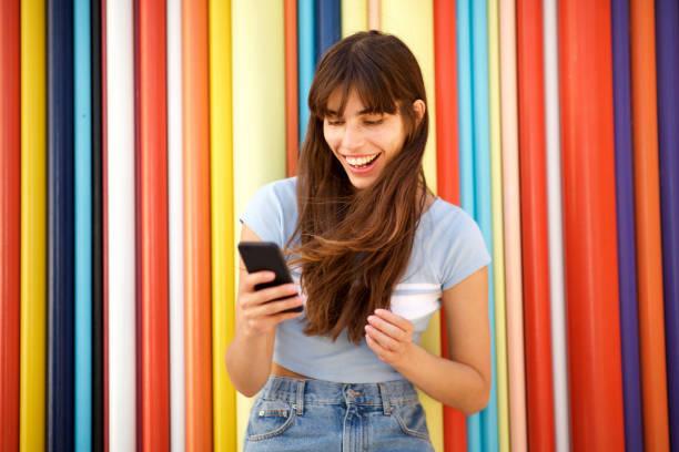 glückliche junge Frau mit langen Haaren blick auf Handy vor buntem Hintergrund – Foto