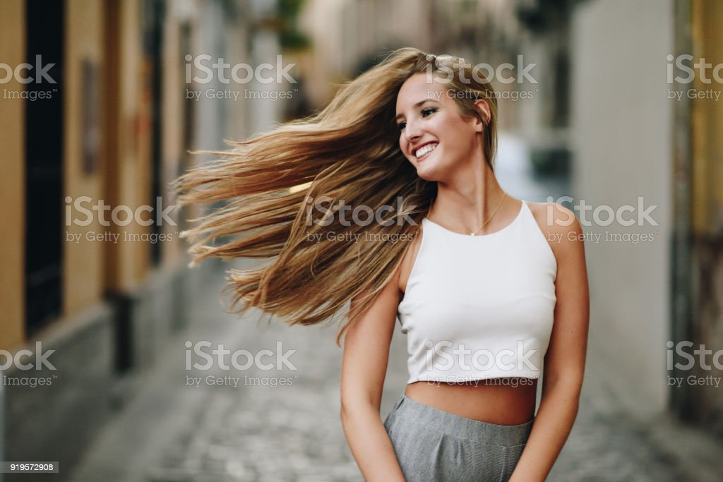 Happy young woman with moving hair in urban background. stock photo