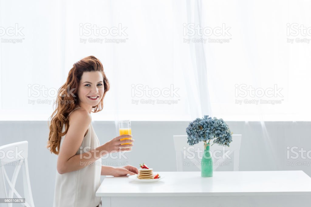happy young woman with orange juice and pancakes with strawberry for breakfast looking at camera stock photo