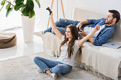 happy young woman with raised arms holding joystick and celebrating victory in video game while her upset boyfriend laying on couch at home