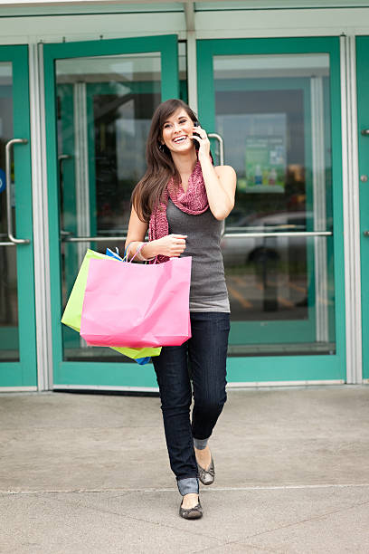 Happy Young Woman with Shopping Bags Leaving Mall stock photo