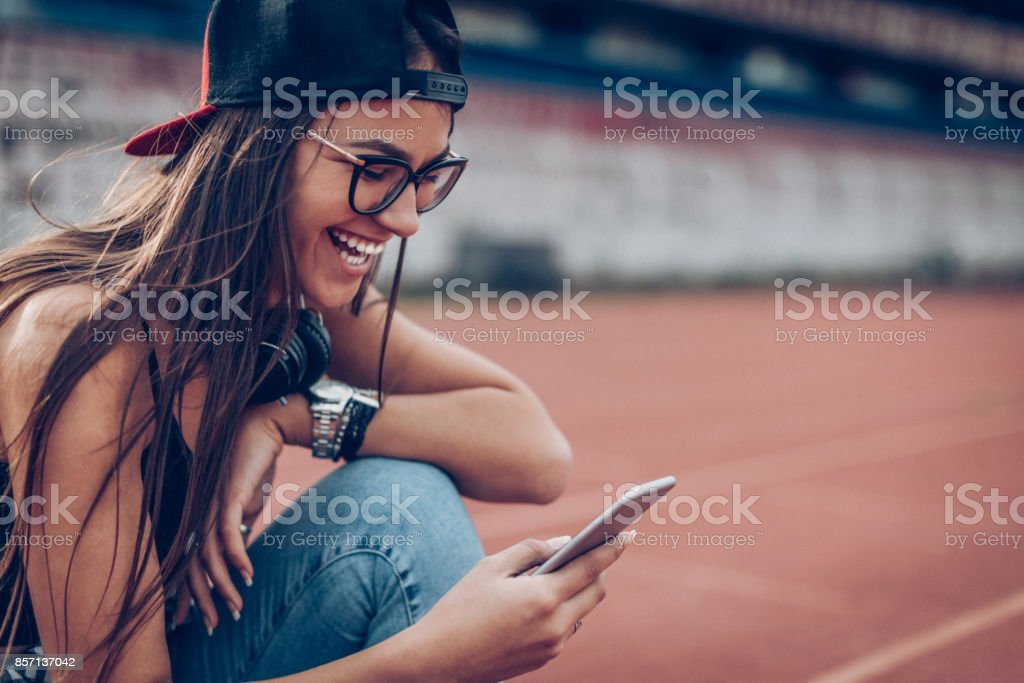 Happy young woman with smart phone stock photo
