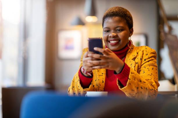 Glückliche junge Frau mit Smartphone in einem Café – Foto