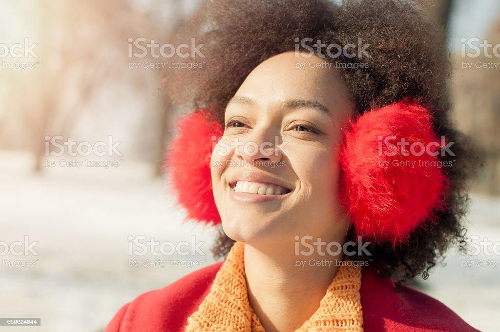Happy young woman with warm on ears enjoying winter sunshine stock photo