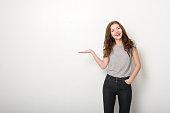 幸せな若い女性にホワイトの壁とカジュアルな服装