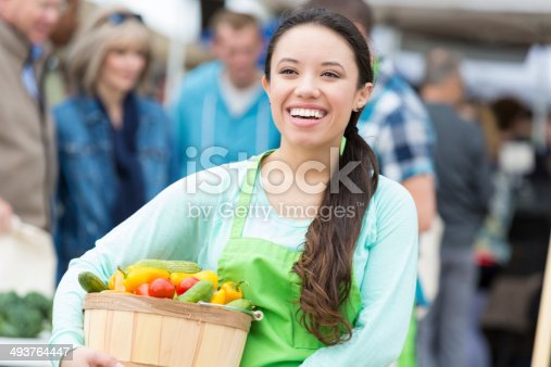 Happy young woman working at outdoor farmers market