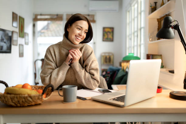 Happy young woman working from home on a laptop stock photo