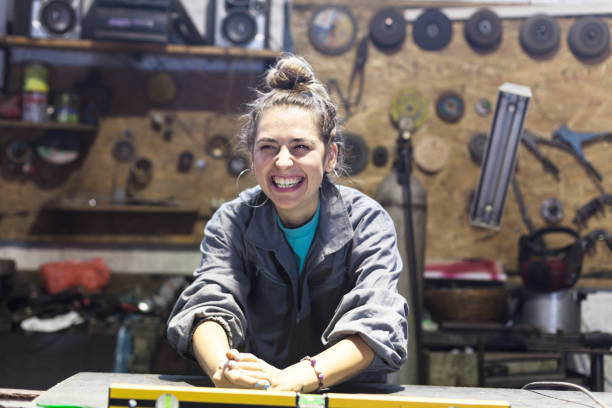 happy young woman working in a workshop young woman working in a workshop apprentice stock pictures, royalty-free photos & images