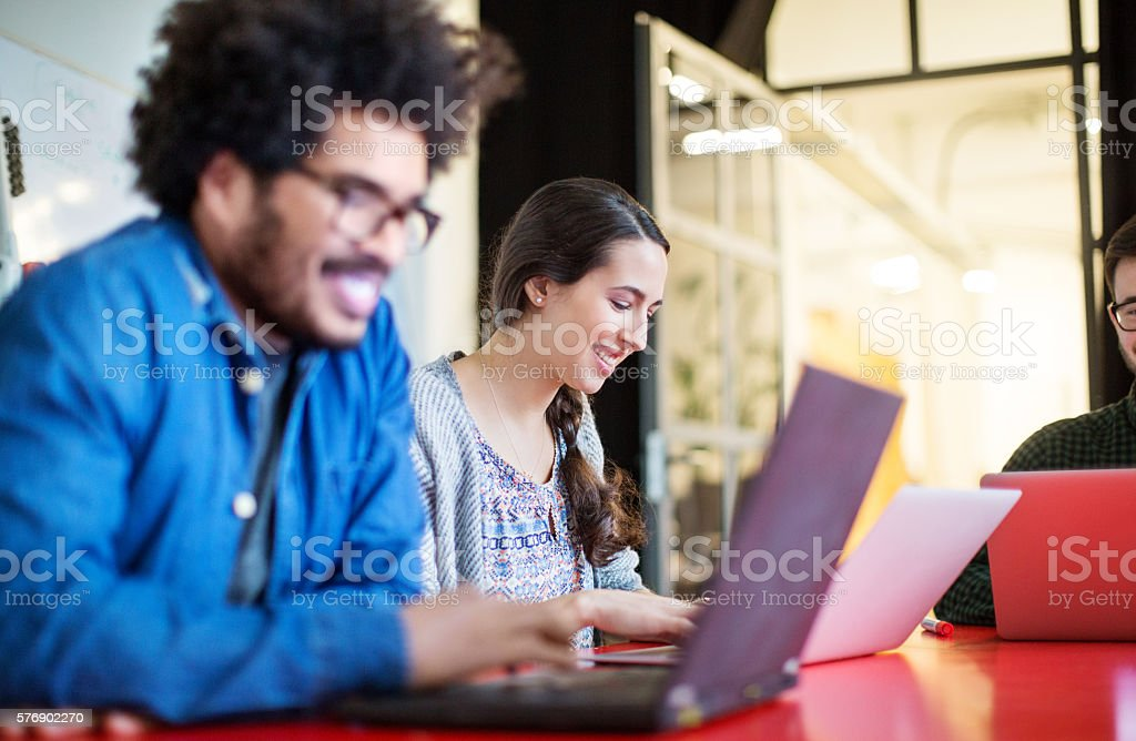 Happy young woman working on laptop with colleagues stock photo