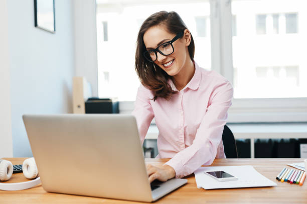 Happy young woman working using laptop in office stock photo