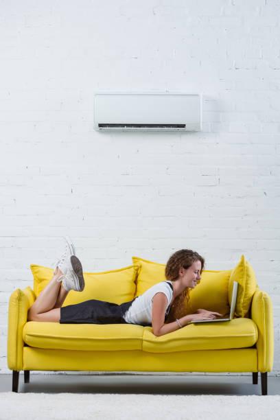 glad ung kvinna som arbetar med laptop liggande på soffan under luftkonditioneringen hängande på väggen - kvinna ventilationssystem bildbanksfoton och bilder