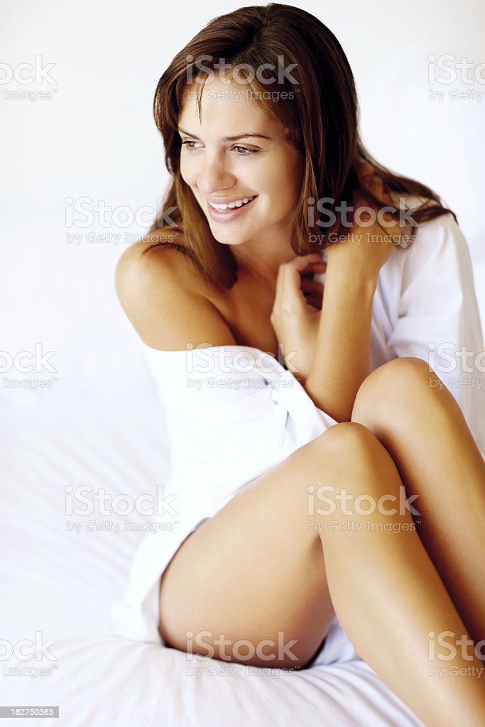 Happy young woman wrapped with a sheet sitting on bed royalty-free stock photo