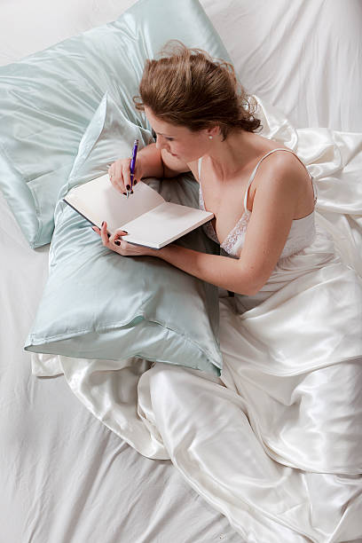 Glückliche junge Frau Schreiben Tagebuch im Bett – Foto