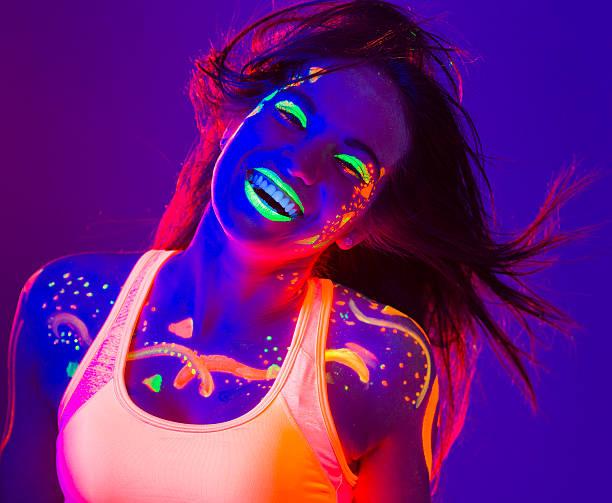glückliche junge frauen, die mit uv-farbe tanz - tanz make up stock-fotos und bilder