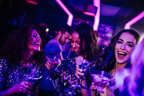 Heureuse jeune femme appréciant un cocktail dans la nuit de fête - Photo