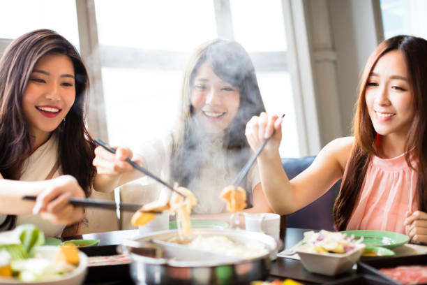 happy young women group  eating hot pot - chinesisches essen stock-fotos und bilder