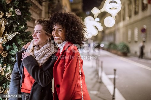 Cheerful Young Female Friends Embracing And Laughing Happily While Having Great Time In Christmas Shopping