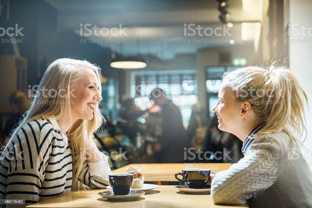 Happy young women looking at each other in cafe stock photo