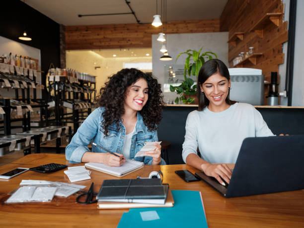 Happy young women sitting at table in store and using laptop stock photo