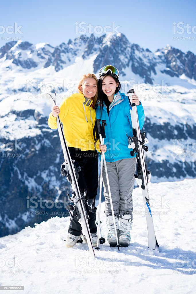 Happy young women skiing stock photo