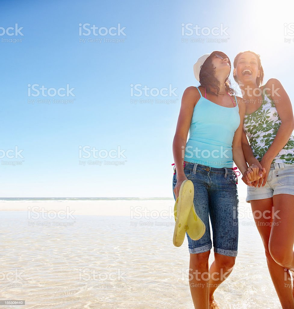 Happy young women standing on the beach royalty-free stock photo