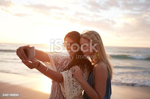 Happy young women enjoying vacation together having fun on the beach and taking selfie photo using smartphone camera.
