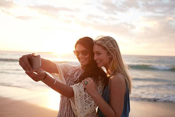 happy young women taking selfie on the beach - schönen abend bilder stock-fotos und bilder