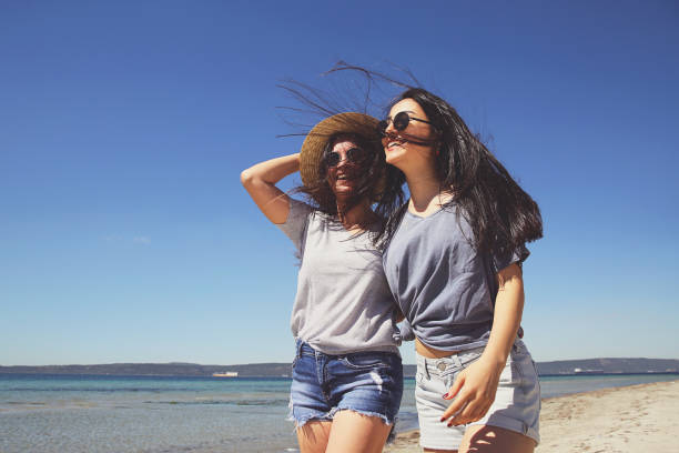 Happy young women walking on a beach stock photo