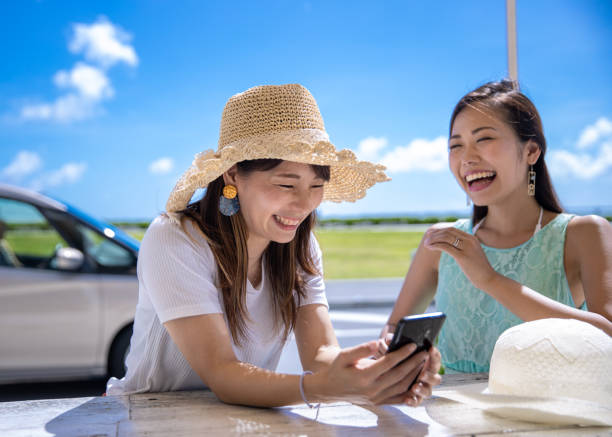 Happy young women watching photos on smart phone Happy young women watching photos on smart phone naha okinawa stock pictures, royalty-free photos & images