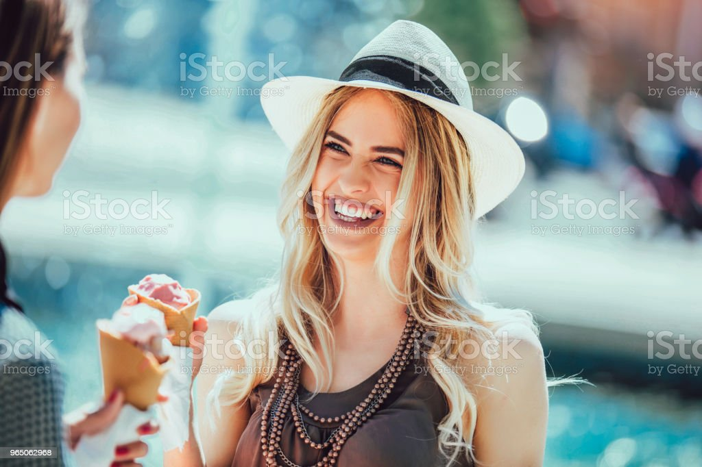 Happy young women with shopping bags and ice cream having fun on city streetshopping bags. royalty-free stock photo