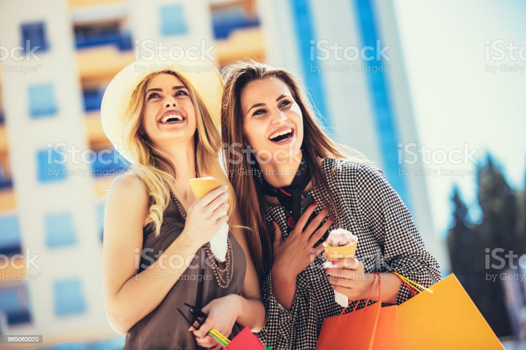 Happy young women with shopping bags and ice cream having fun on city streetshopping bags. zbiór zdjęć royalty-free