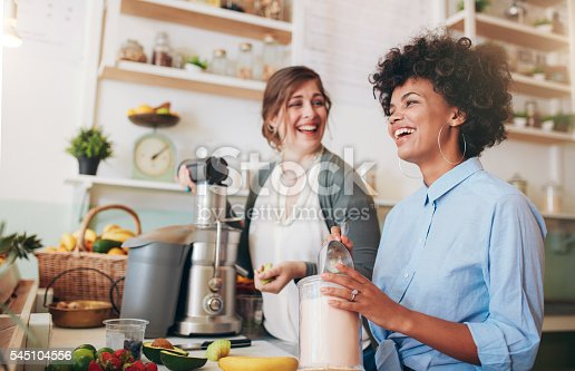 istock Happy young women working at juice bar counter 545104556