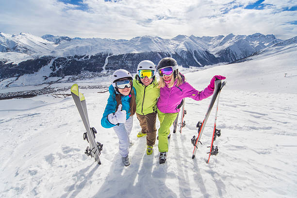 Happy youth in colorful jackets ski alps resort Female and male young people having skiing and snowboarding vacation on a snow slopes  ski holiday stock pictures, royalty-free photos & images