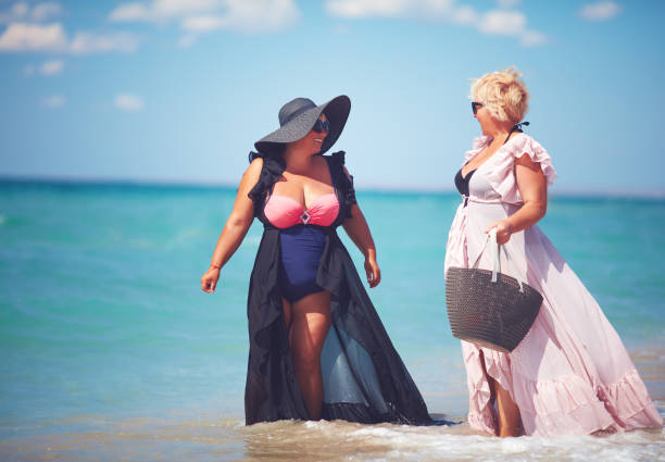 happyadult women enjoy summer vacation at the beach happy adult women enjoy summer vacation at the beach middle aged women in bikinis stock pictures, royalty-free photos & images