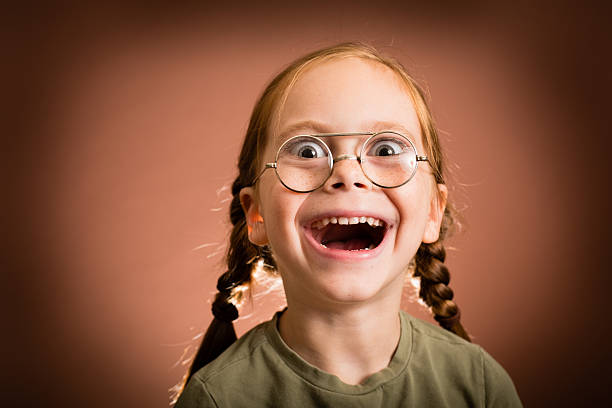 """Happy/Excited Little Girl Wearing Nerdy Glasses """"Color image of a young girl with red hair, wearing nerd glasses, with brown background."""" nerd hairstyles for girls stock pictures, royalty-free photos & images"""