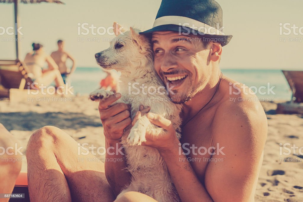 Happyman with a puppy in his arms stock photo