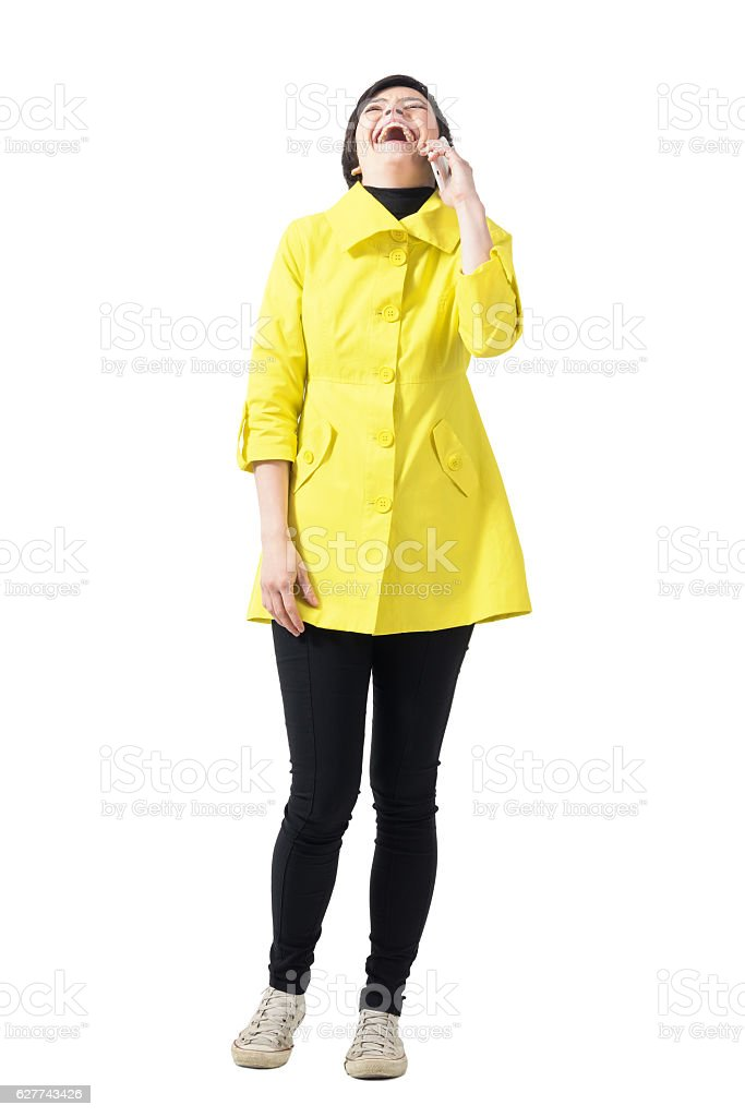 Happywoman in yellow coat laughing loudly on the mobile phone stock photo