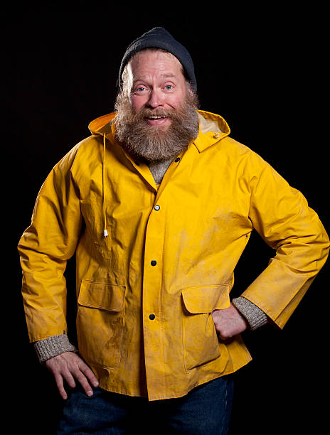 hapy fisherman A middle aged fisherman wearing a yellow rain slicker and a hat with a big beard laughs at something. fisherman stock pictures, royalty-free photos & images