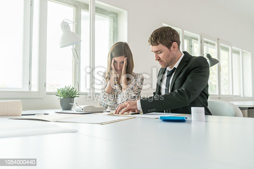 690496350istockphoto Harassed businesswoman checking the accounts 1054000440
