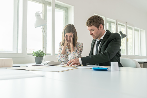 690496350 istock photo Harassed businesswoman checking the accounts 1054000440