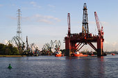 Oil platform and 4 tug bots on harbor background.